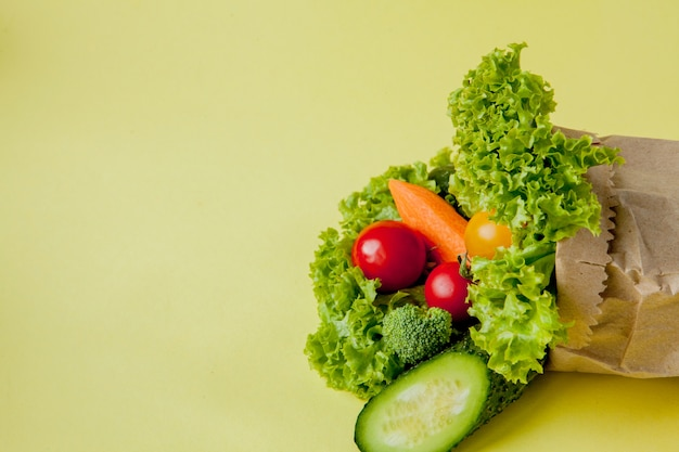 Organic vegetables broccoli cucumbers bell peppers apples in brown paper kraft grocery bag