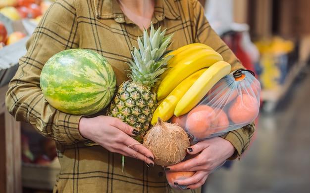 有機野菜をクローズアップ。スーパーで買い物や新鮮な有機野菜を買うの美しい若い女性