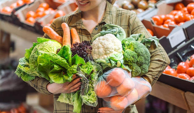 Organic vegetables close up. beautiful young woman shopping in a supermarket and buying fresh organic vegetables