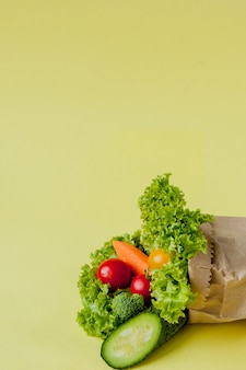 Органические овощи огурцы болгарские перцы яблоки в коричневой бумаге продуктовый мешок kraft на желтой предпосылке. здоровая диетическая диетическая клетчатка без веганского пластика. плакат баннер