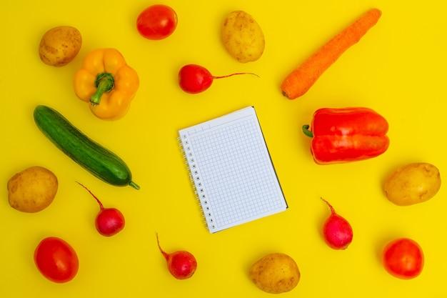 黄色の背景に有機野菜。買い物リスト