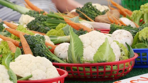 カウンターにある有機野菜、市場の屋台にある新鮮な地元産の生野菜。健康的なベジタリアン料理、米国カリフォルニア州オーシャンサイドのファーマーズマーケット。農業農家の収穫販売。