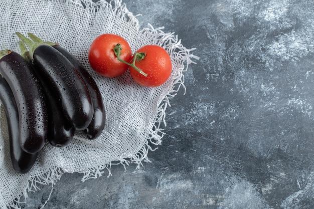 有機野菜。灰色の背景にトマトと紫のナス。