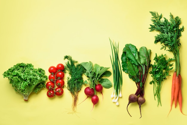Organic vegetables on yellow background with copy space.