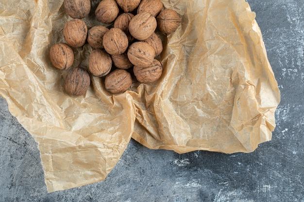 Organic walnuts on brown paper sheet.
