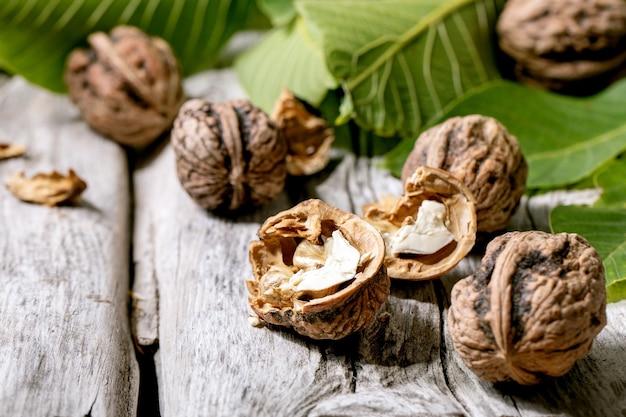 Органические грецкие орехи, целые и сломанные, с зелеными листьями орехового дерева над старым деревянным столом. закрыть вверх