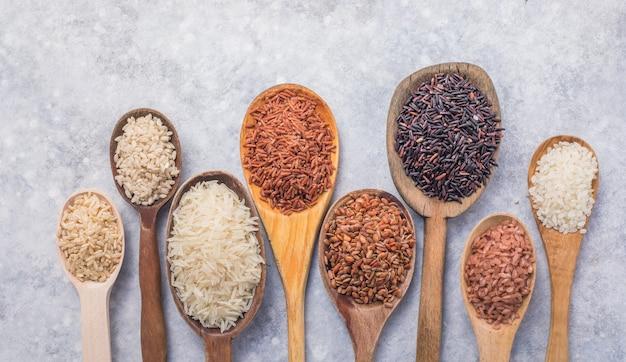 유기농 흰색 재스민 쌀, 닦지 않은 흑미 및 현미, 나무 숟가락에 담긴 riceberry