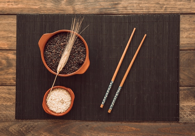 Organic white and red rice with stalk and chopsticks on wooden tray