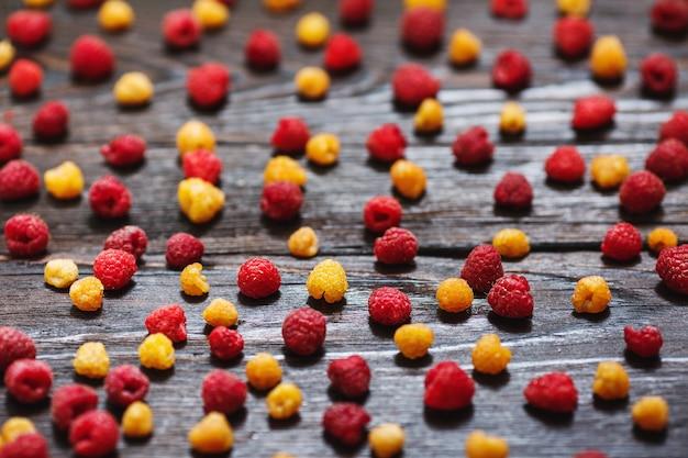 Органические желтые и красные малины смешались на деревянных фоне.