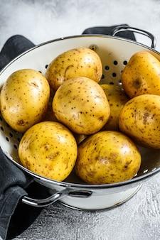 Органический желтый картофель на дуршлаге. серый фон. вид сверху.