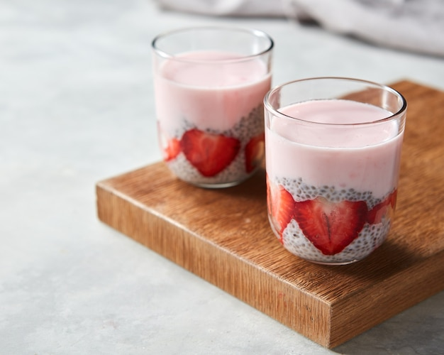 Organic yogurt smoothie with strawberries and chia seeds, fruit dessert on wooden board on grey