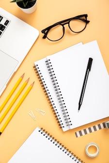 Disposizione organizzata degli elementi dello scrittorio su fondo arancio