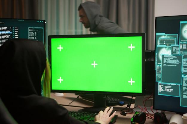 Организованный женский хакер перед компьютером с зеленым экраном.