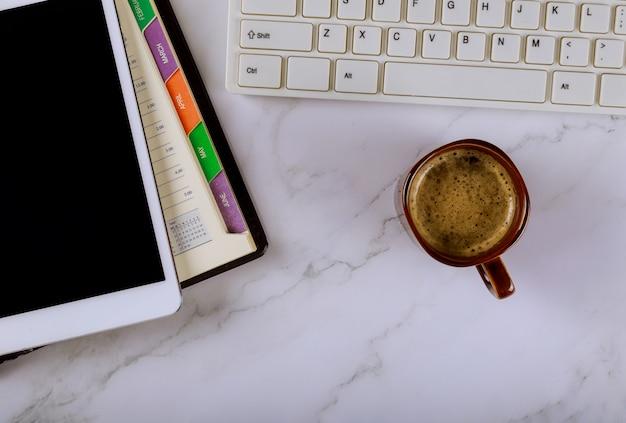 カップコーヒーとデジタルタブレットのキーボードで組織管理プランナーの毎週カレンダー