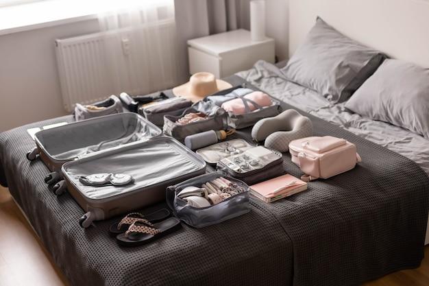 Организация хранения необходимых вещей в удобном футляре методом конмари на кровати.