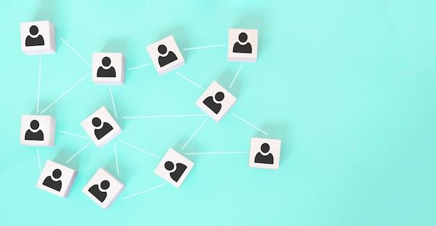 組織構造、チームビルディング、経営管理、または人事の概念。互いにリンクされている木製の立方体の人のアイコン。