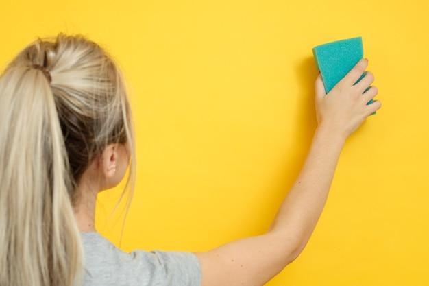 組織化された家の掃除。染みのないクリーニング。スポンジ拭き想像上のスポットを持つ女性。