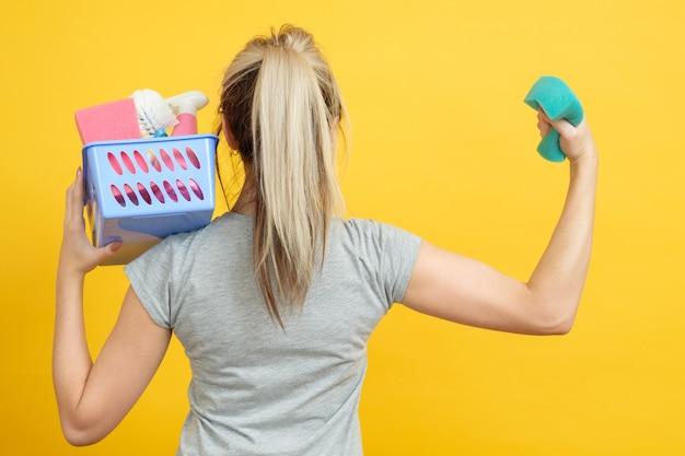 組織された主婦。ハウスキーピングのコンセプト。黄色の上腕二頭筋を示すクリーニング用品のバスケットを持つ女性。