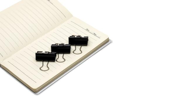 白いコピースペースのある開いたノートブックに3つのバインダークリップを整理しました