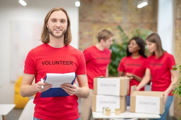 조직 된 자원 봉사자. 기부금 상자 근처의 손과 동료에 문서와 마커가있는 빨간색 자원 봉사 tshirt의 젊은 장발 남자