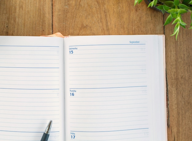 Organizer and pen on wooden table background -business planning.