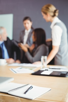 Organizer with pen on table in conference room