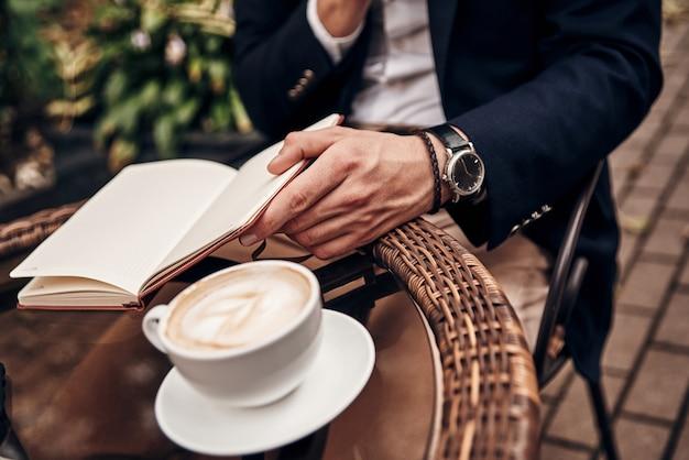 매분 정리. 야외 레스토랑에 앉아 있는 동안 개인 주최자를 열어 두는 스마트 캐주얼 차림의 젊은 남성 클로즈업