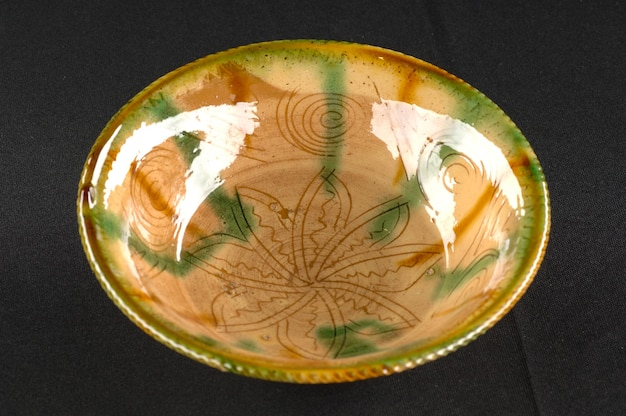 Восточная античная керамическая тарелка на черном фоне крупным планом