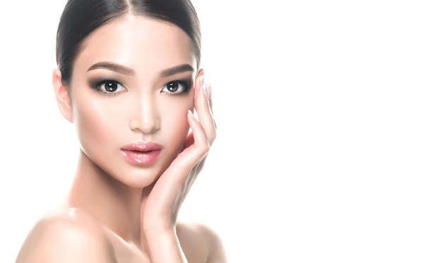 Oriental beautygorgeous young asian black haired woman with clean fresh skin and delicate makeup is touching the face