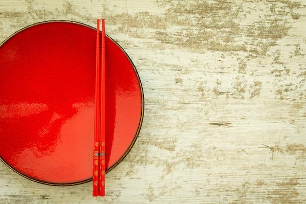 Oriental ceramic plate and chopsticks in red