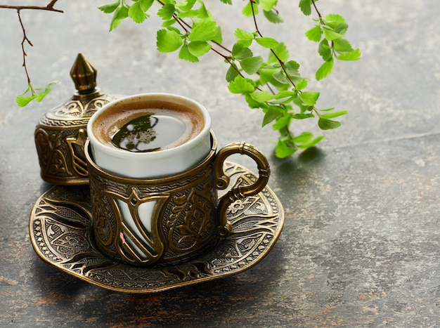 Oriental coffee cooked in traditional turkish copper coffee pot poured in a cup