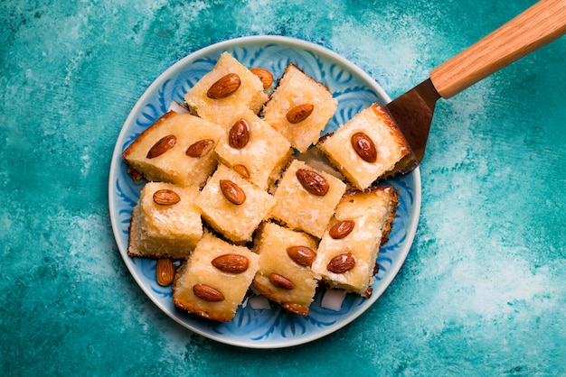 青いプレート上のシロップ、ココナッツ、アーモンドアラビアバスバスと東洋料理菓子セモリナパイ