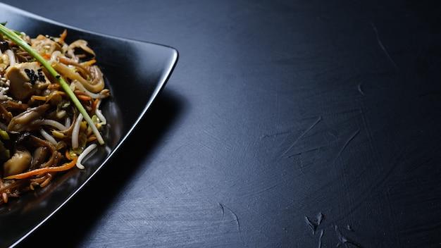 동양 요리 음식입니다. 건전한 건강한 식생활. 어두운 배경에 야채 샐러드입니다. 카피스페이스 개념