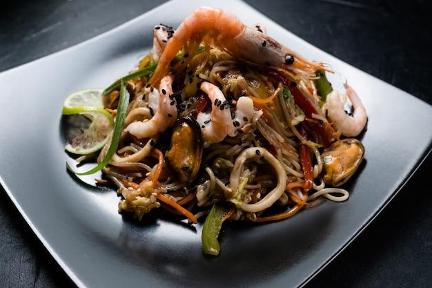 Еда в ресторане восточной кухни. лапша креветки креветки морепродукты и овощи на тарелке.