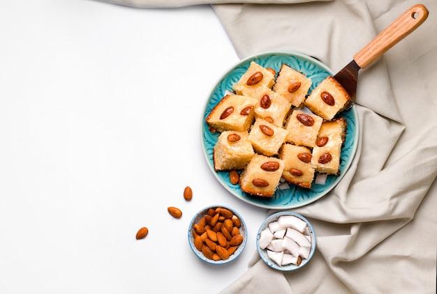 白い背景の青いプレートに東洋料理甘いアラビア語のbusbusセモリナパイ