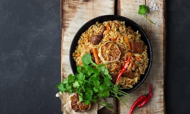 Восточная кухня. узбекский плов или плов из риса и мяса в чугунной сковороде на деревянной деревенской доске. вид сверху с копией пространства.