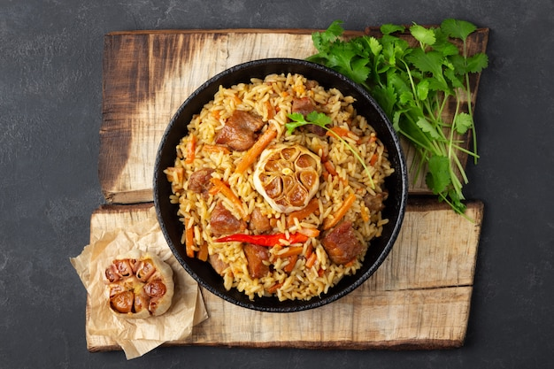 Восточная кухня. узбекский плов или плов из риса и мяса в чугунной сковороде на деревянной деревенской доске. вид сверху.