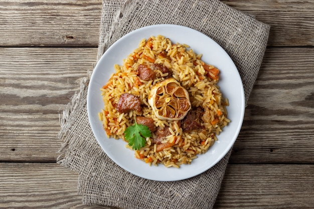 Oriental cuisine. uzbek pilaf or plov from rice and meat. wooden rustic background. top view vith copy space.