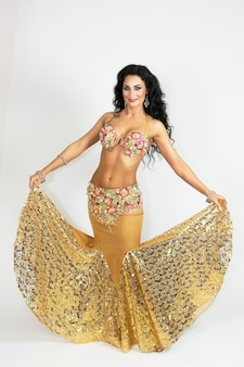 Oriental dancer in clothes of gold color with black hair and bronze skin gracefully posing a white