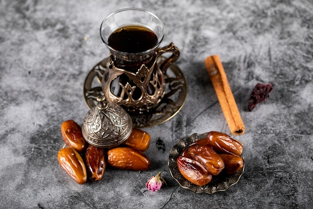 Oriental dates in an ethnic style saucer with a glass of tea and cinnamon sticks.
