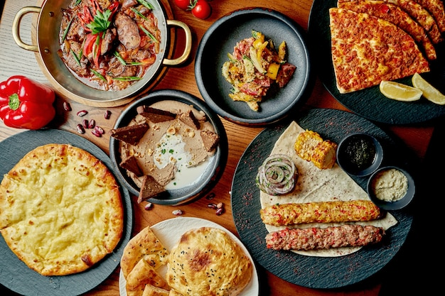 Восточный обеденный стол с пиде, кебабом, хачапури, салатом. вид сверху на семейный стол из разных блюд
