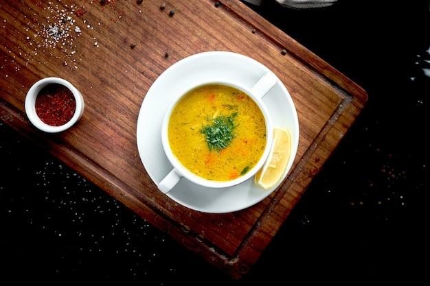 オリエンタル料理-暗いテーブルピアラに白の黄色いレンズ豆クリームスープ