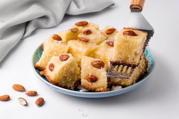 明るい背景にセモリナ粉と東洋料理の甘いケーキ。ワンピースがケーキヘラにあるところ
