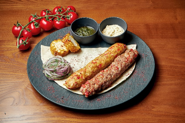 An oriental dish two chicken and lamb kebab from minced meat with lavash and green sauce. halal food