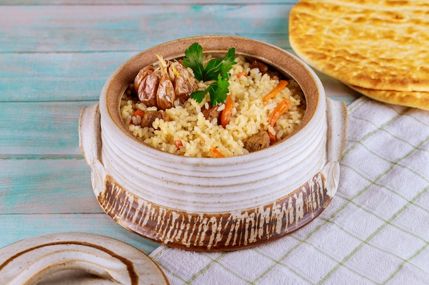Oriental dish with rice, carrot, garlic and meat.