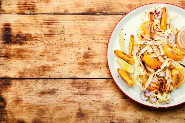 オリエンタル料理、古い木製のテーブルに麺と柿のサラダ