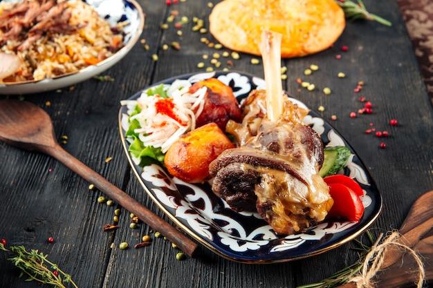 ジャガイモ伝統的なプレートと東洋の子羊の脚