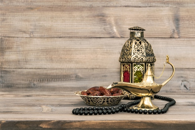 Oriental lamp and dates on wooden table. festive still life with rosary