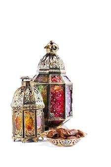 オリエンタルライトランタンとナツメヤシの甘い食べ物。アラビアの休日の装飾。ラマダンカリーム。エイド・ムバラク