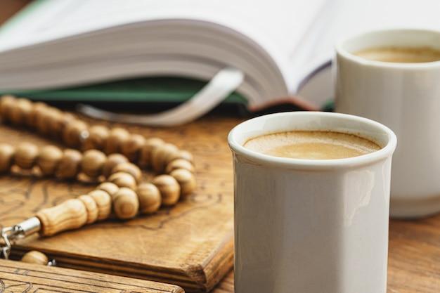 東洋の宗教的なビーズがコーヒーと木製のテーブルにクローズアップ